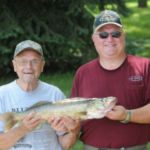 two men hold up walleye