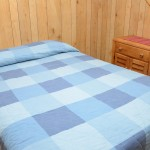 bed with blue quilt