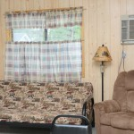 futon and recliner in wood paneled room