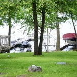 view of lawn boats and lake